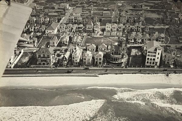 Leme, por José Augusto de Paiva Meira (c. 1921). Piloto de hidroaviões da Marinha, o fotógrafo produziu diversas imagens aéreas da cidade. Detalhe: parte do calçadão, à direita, havia sido destruída por uma ressaca