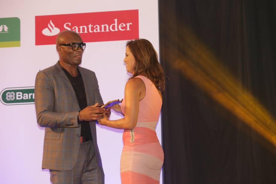 O lutador Anderson Silva entrega o prêmio na categoria Filantropia para Renata Guerra