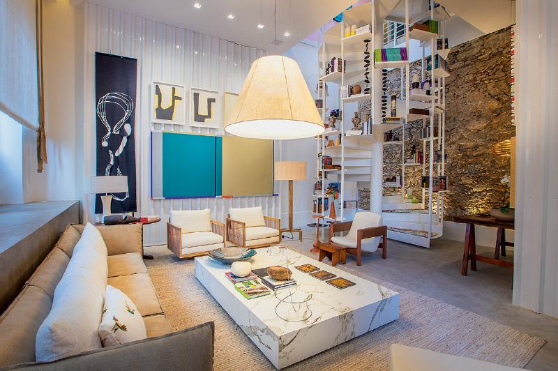 No Estúdio dos Colecionadores, de Mauricio Nóbrega, telhas metálicas revestem paredes e a escada ganhou prateleiras com livros e almofadas removíveis