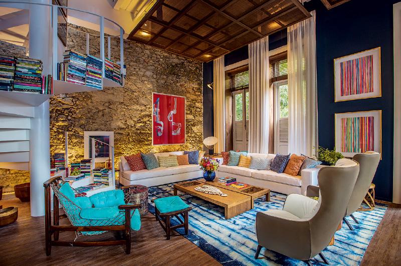 O living da praia, de Paola Ribeiro, valoriza tons azuis, que contrastam com almofadas e livros coloridos. Uma tela de palha foi usada para forrar o teto e a parede de pedras foi mantida