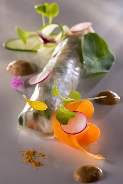 Enrolado de legumes e flores na folha de arroz, servido com molho de castanha-de-baru