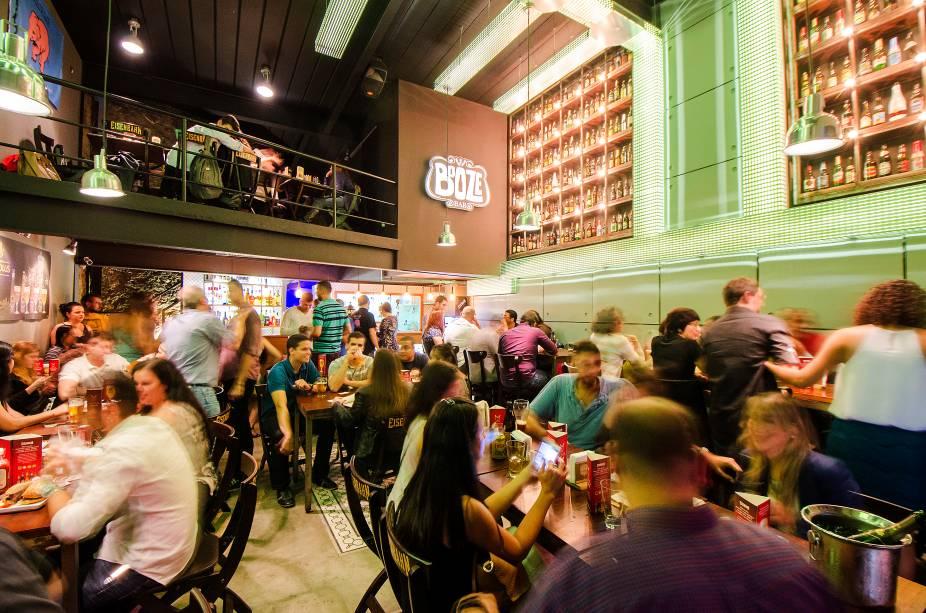 O agradável salão do Booze Bar tem garrafas nas paredes, iluminação em tons verdes e mezanino: bela novidade no coração da Lapa