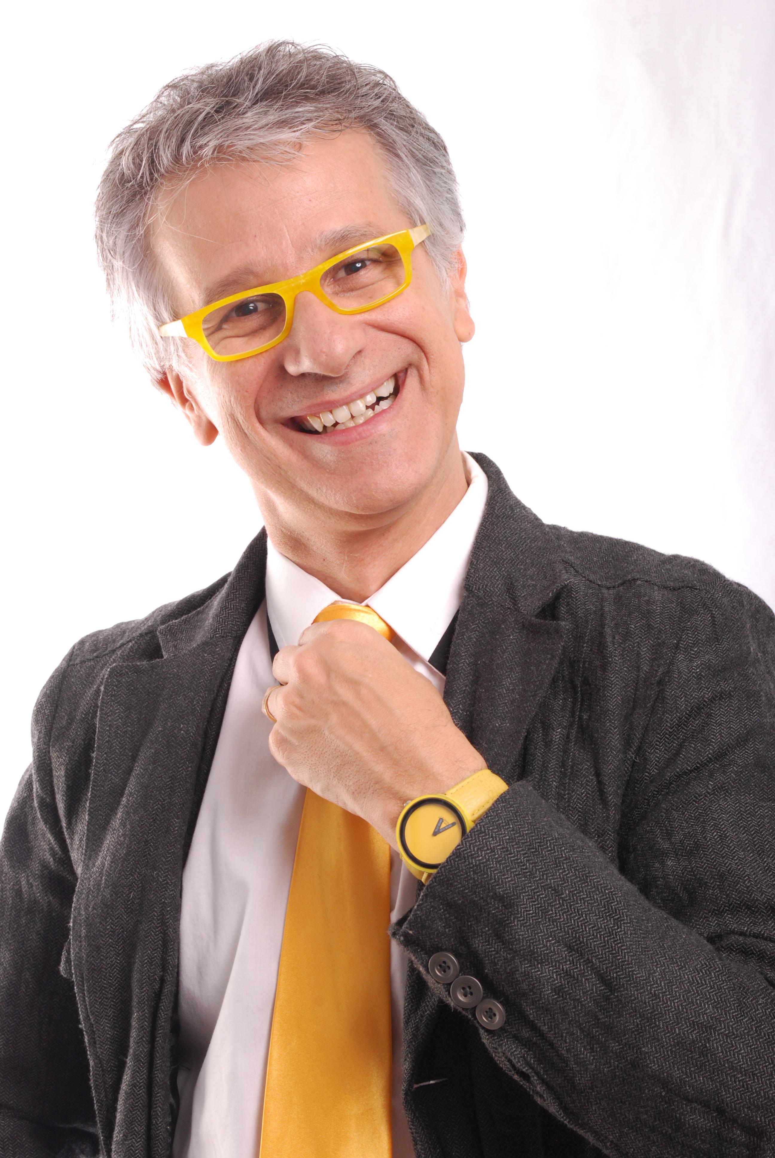 Claudio Torres Gonzaga, de terno, com a mão na gola, sorrindo