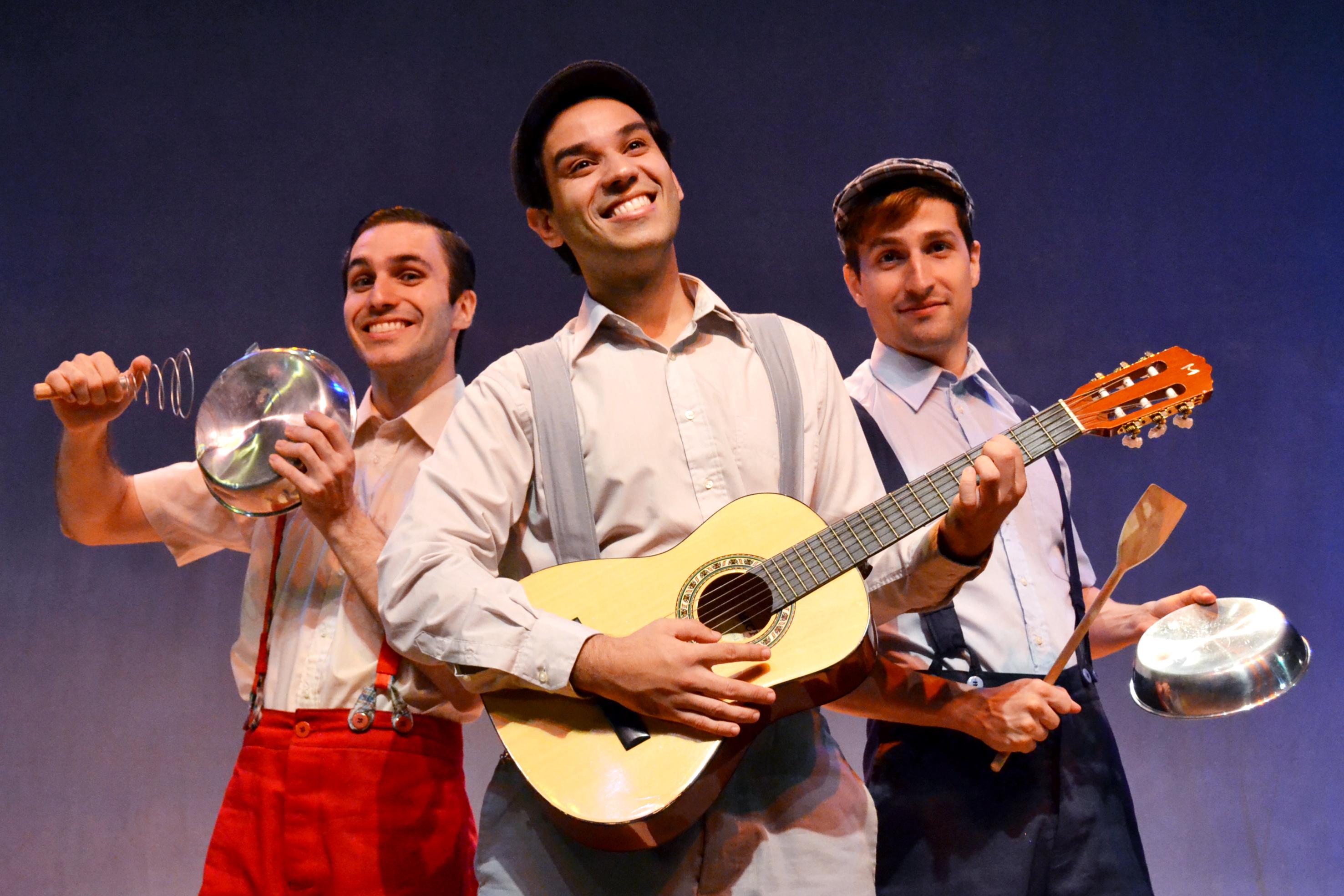 Tres atores no palco, com roupas de época e instrumentos musicais