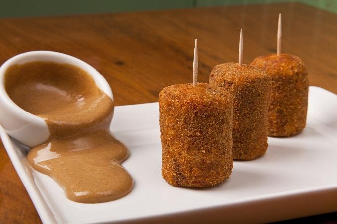 Mini croquetes de carne recheados com queijo e servidos com molho de mostarda são boa opção de entrada disponível no menu promocional<br>