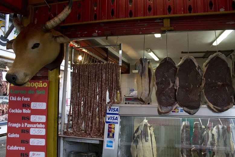 """Em um dos poucos açougues da feira, é possível encontrar a autêntica carne de sol, além de mocotó e costela. Mas o chamariz mesmo é a cabeça de boi (de mentirinha) pendurada do lado de fora do estabelecimento. """"Tem mais turista parando para tirar foto do<br>"""