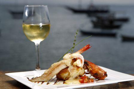 Peixe grelhado, concassê de tomate sobre blinis de cará trufado e camarão banhado em espuma de cupuaçu.<br>
