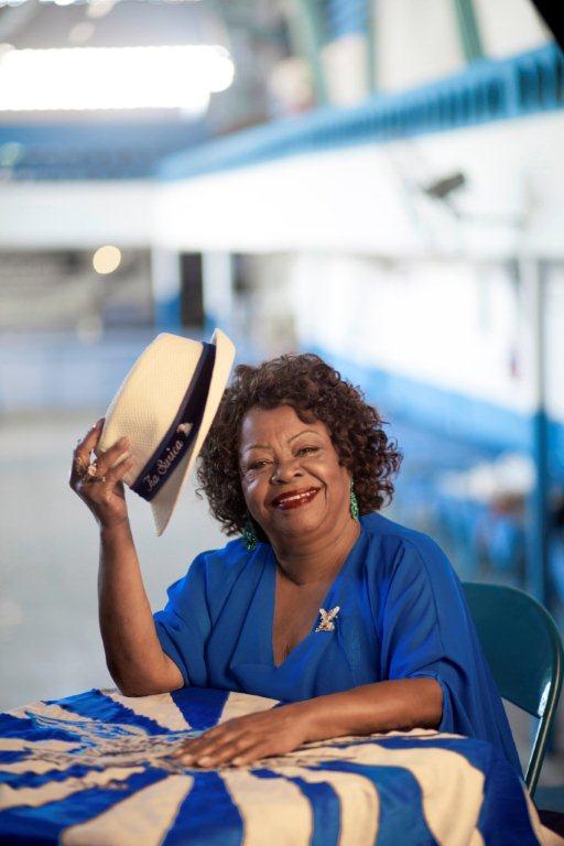 Tia Surica acenando com um chapéu panamá na quadra da Portela