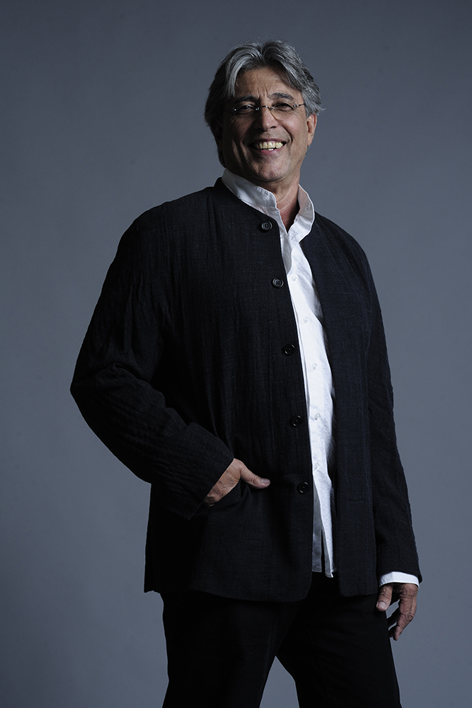 Ivan Lins, de paletó, com a mão no bolso, sorrindo