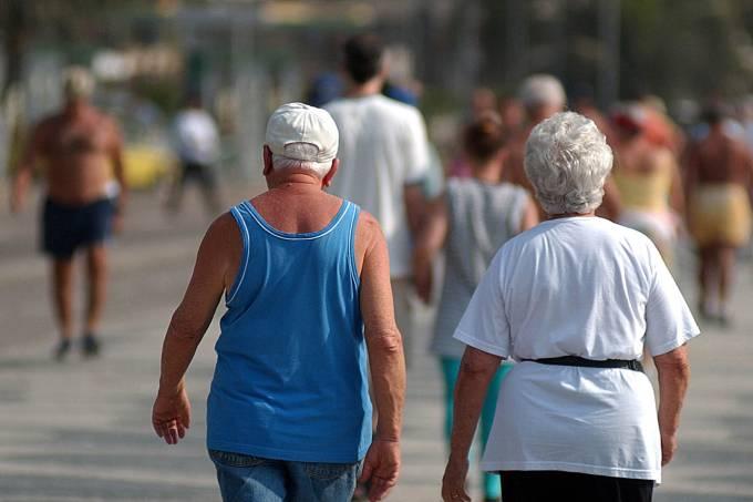 Pessoas caminhando no calçadão da Praia de Copacabana.