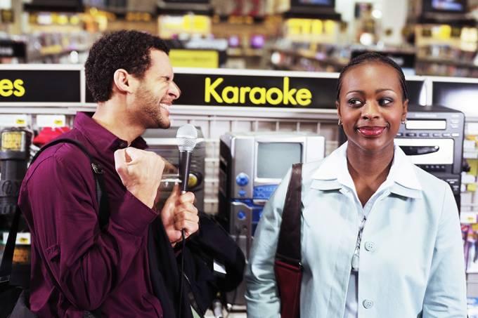 Homem cantando em loja de eletrônicos.