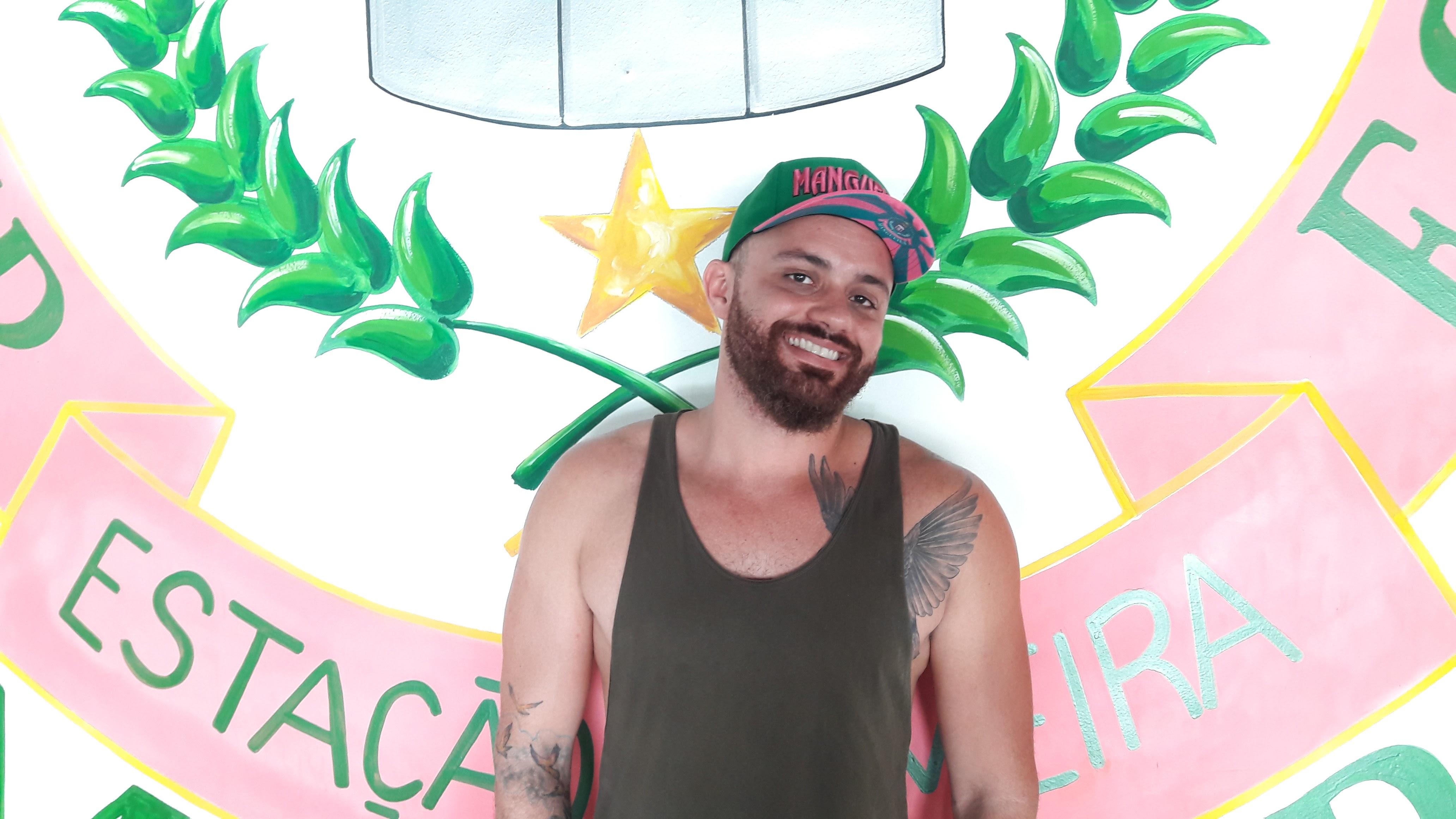 Carnavallesco da Mangueira sorri em frente a uma pintura do bandeira da escola
