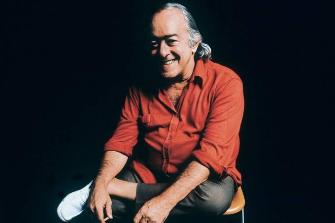 Vinícius de Moraes sentado numa cadeira segurando um cigarro.