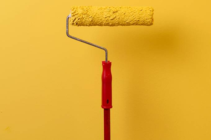 Paint Roller Painting The Wall In Yellow