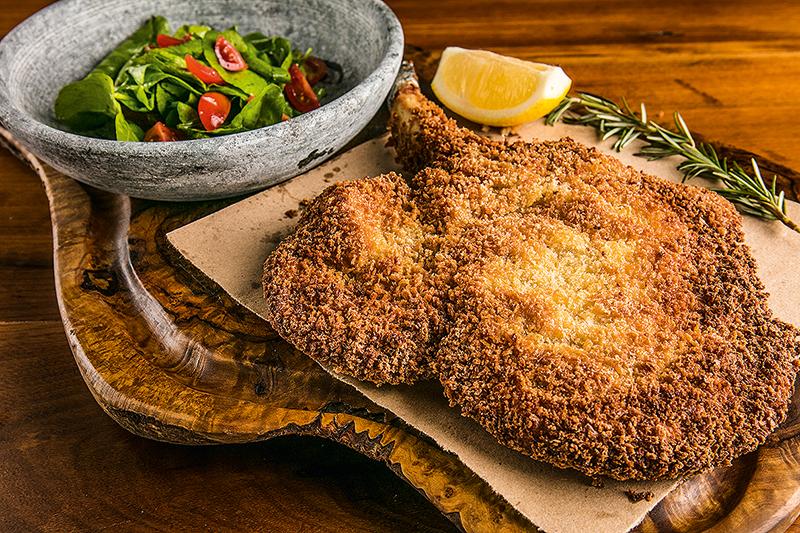 Carré suíno à milanesa, ladeado por salada de rúcula com tomate