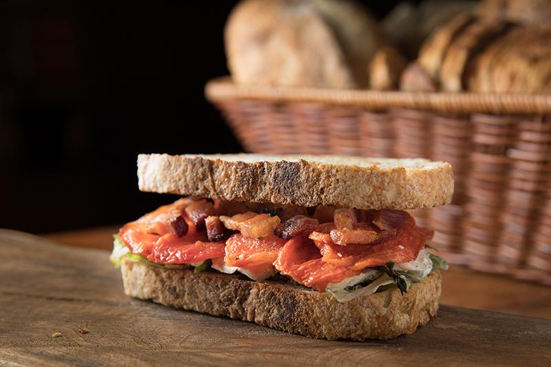 <span>O club sandwich tem recheio de peito de frango, alface, sálvia, maionese caseira, tomate confit e bacon</span>