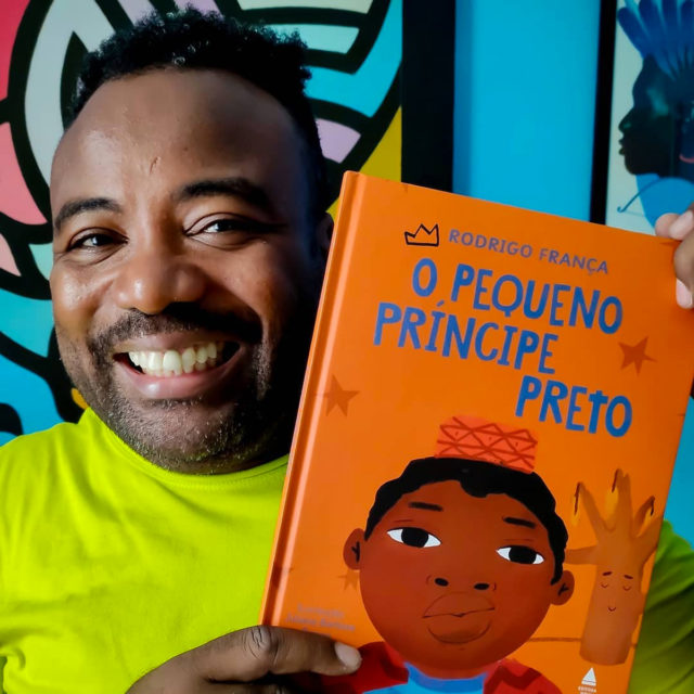 Rodrigo França segura o livro O Pequeno Principe Preto e sorri