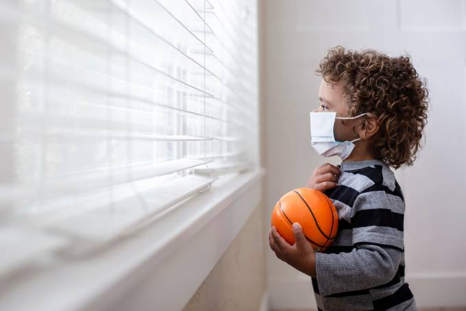 A young boy looking out the window wearing a protective facemark while seeking protection from COVID-19