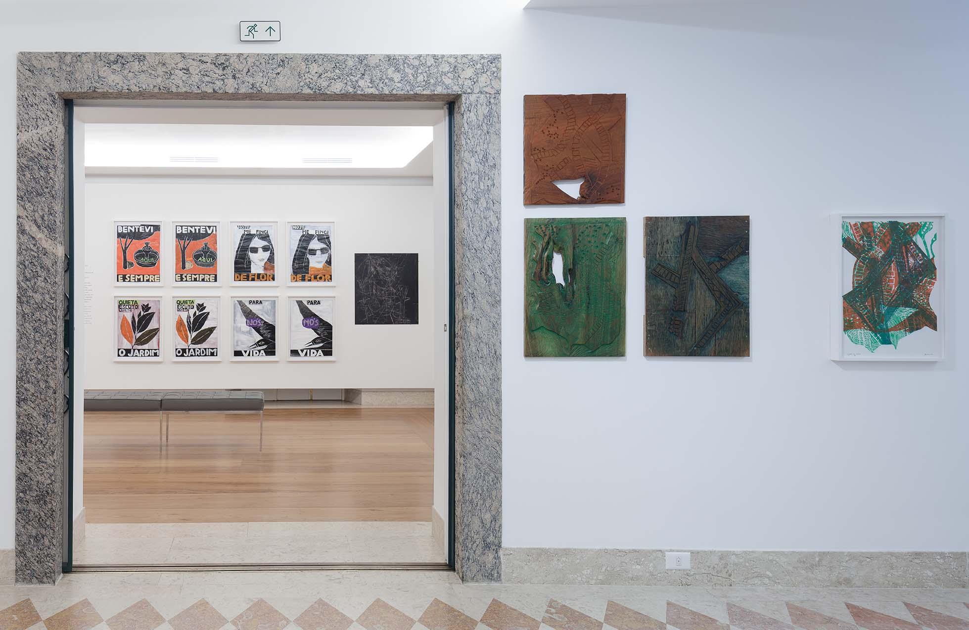 Parede da Casa Roberto Marinho com três quadros. Ao fundo, sala de exposição com diversos quadros presos à parede