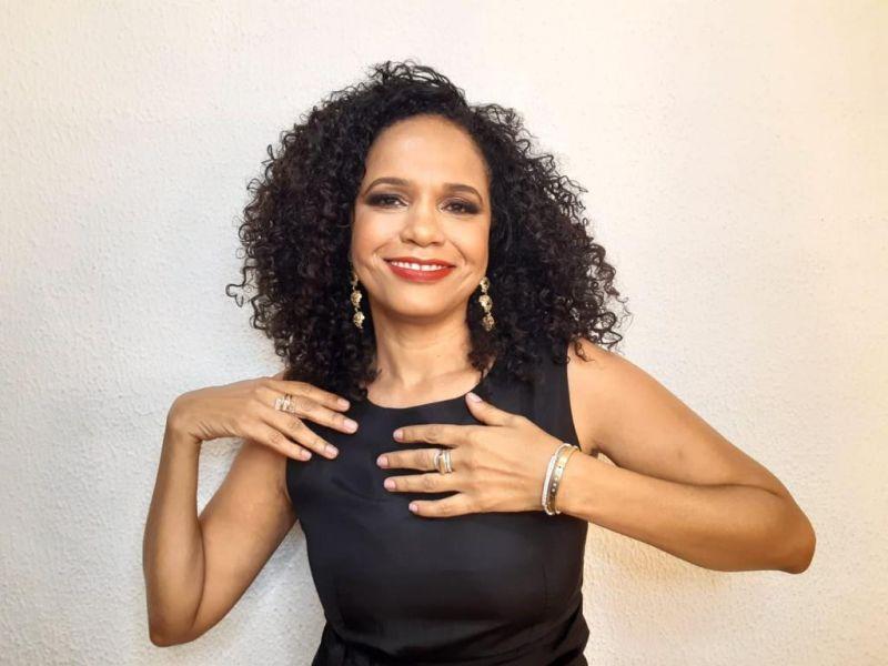 Teresa Cristina sorrindo, com as mãos próximas ao peito