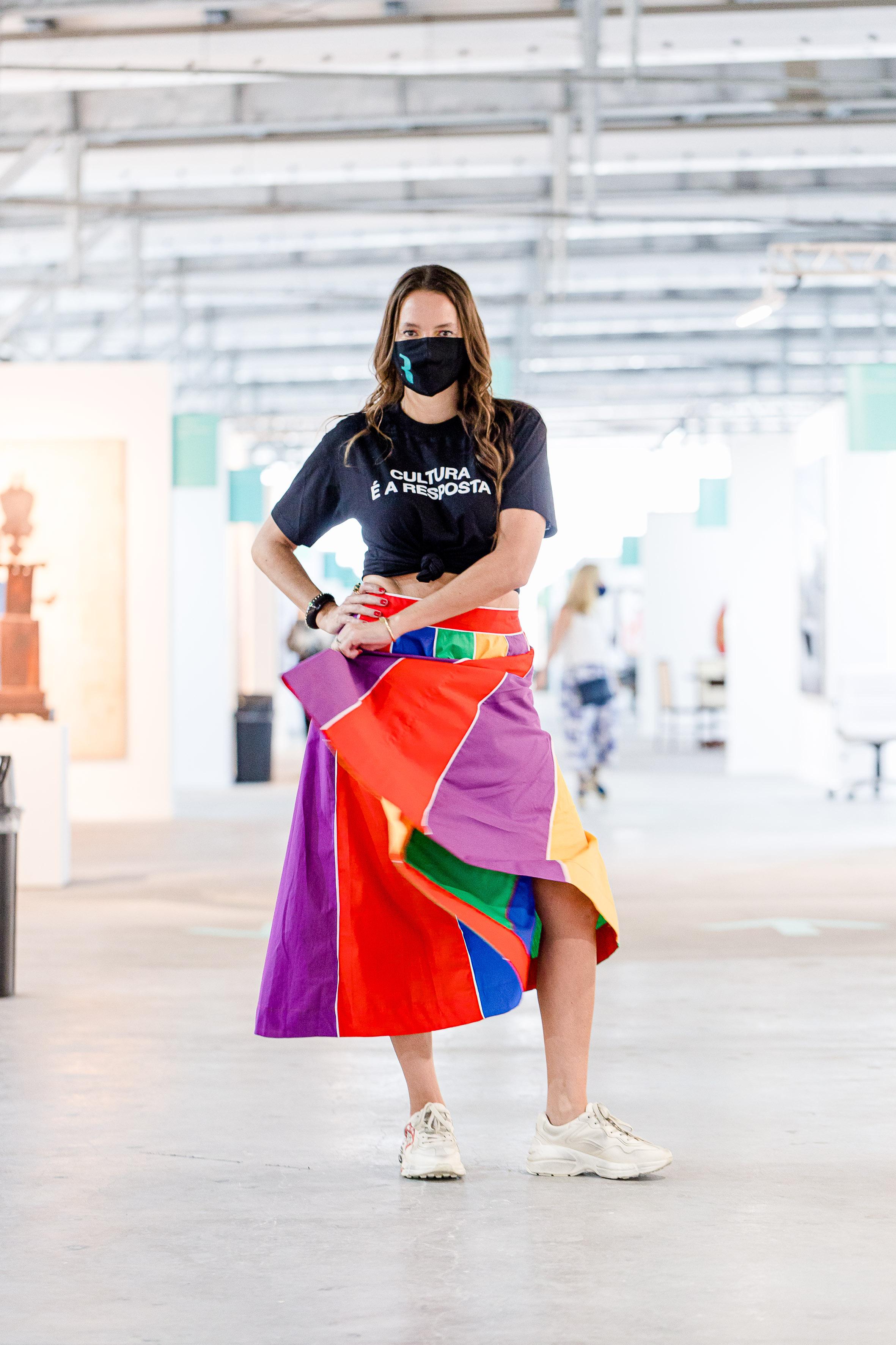 Brenda Valansi, de roupa colorida e máscara facial, na ArtRio de 2020