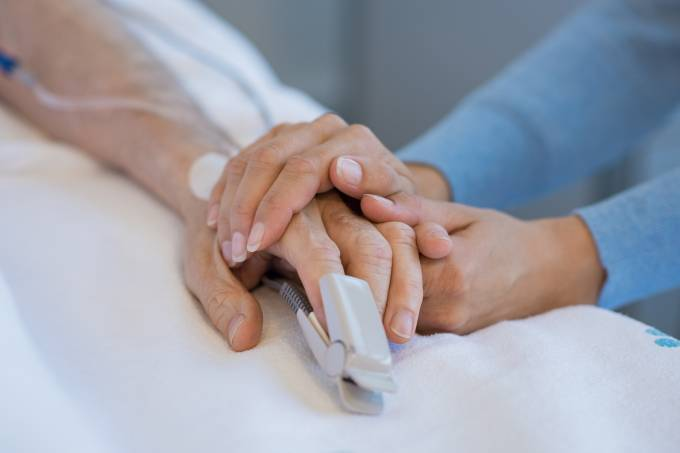 Daughter holding the hand of an elderly father. Closeup of woman