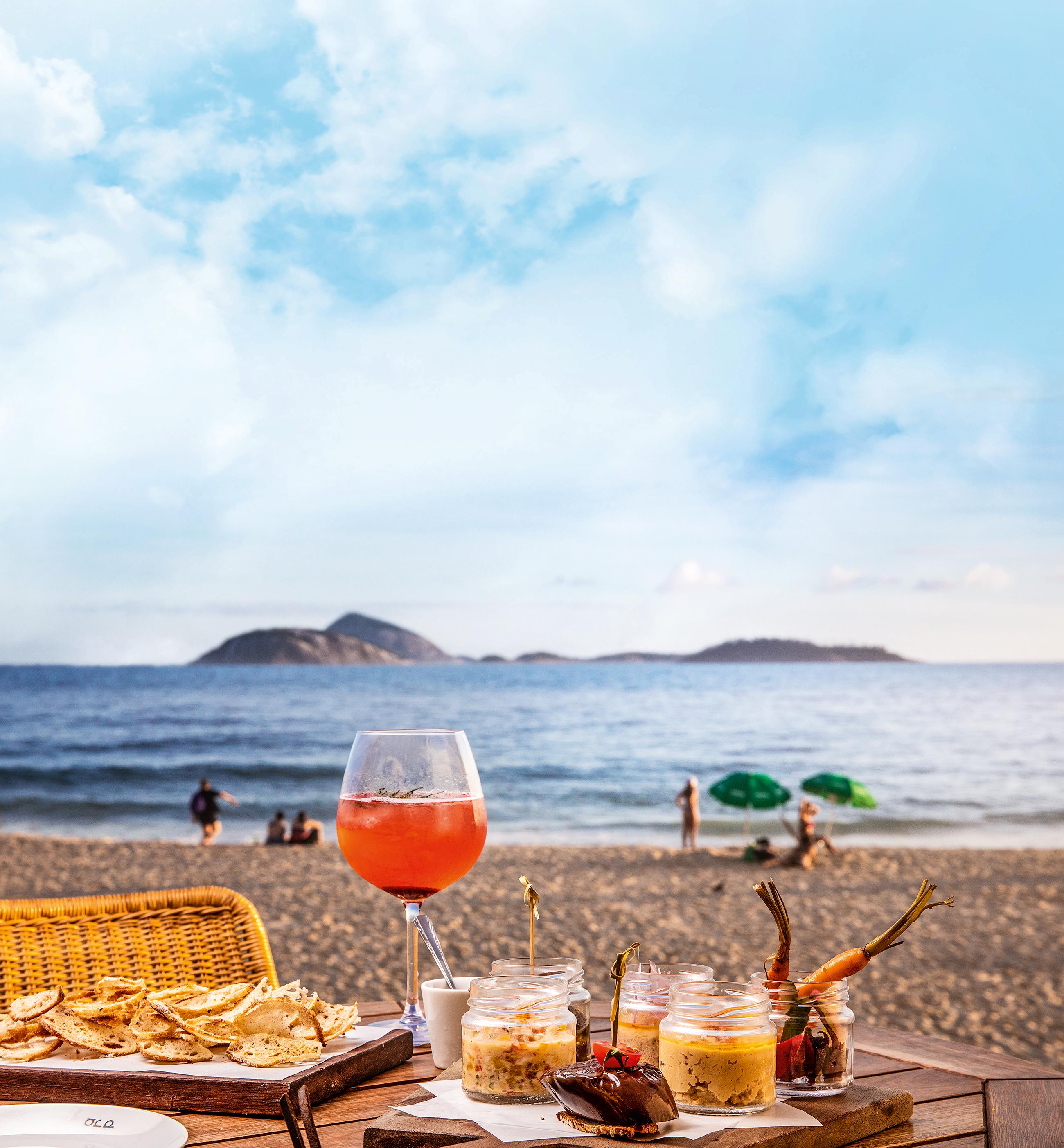 Mesa posta com petiscos e drinque em frente à praia do Arpoador