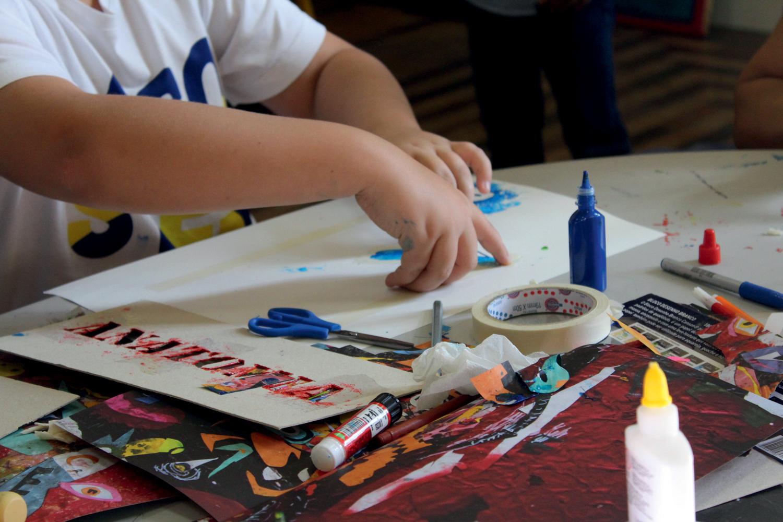 braços de criança fazendo pintura. papéis coloridos, cola e tinta espalhados pela mesa
