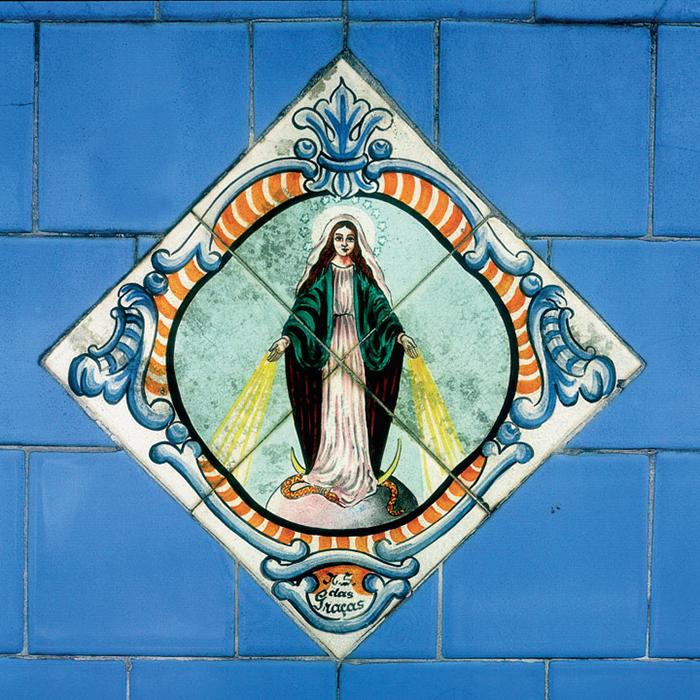 Fotografia de azulejo mostra imagem de Nossa Senhora com raios saindo das mãos