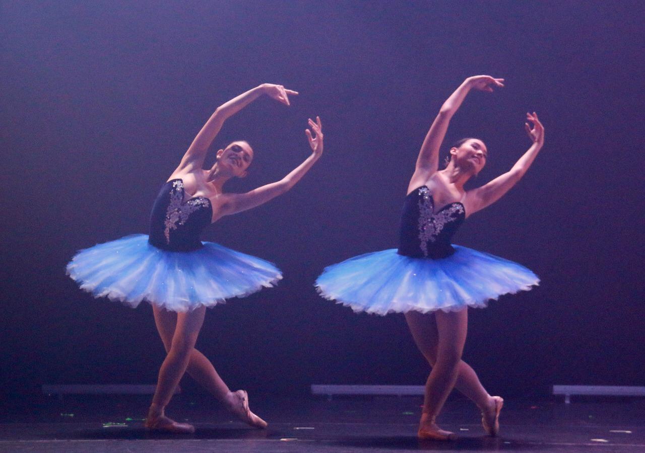 Duas bailarinas no palco, fazendo passos de balé, inclinadas para a esquerda