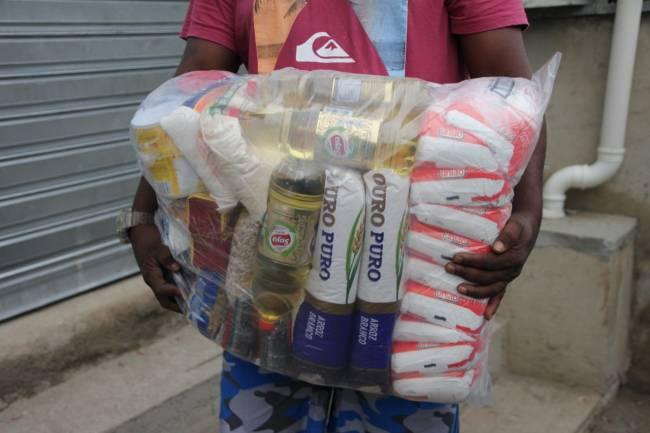 Homem carrega alimentos como arroz, óleo e feijão