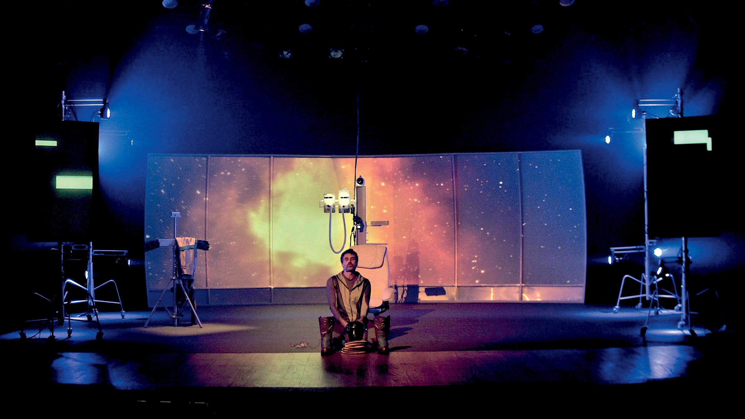 O ator Eriberto Leão no palco da peça O Astronauta, com um telão ao fundo que simula o espaço sideral