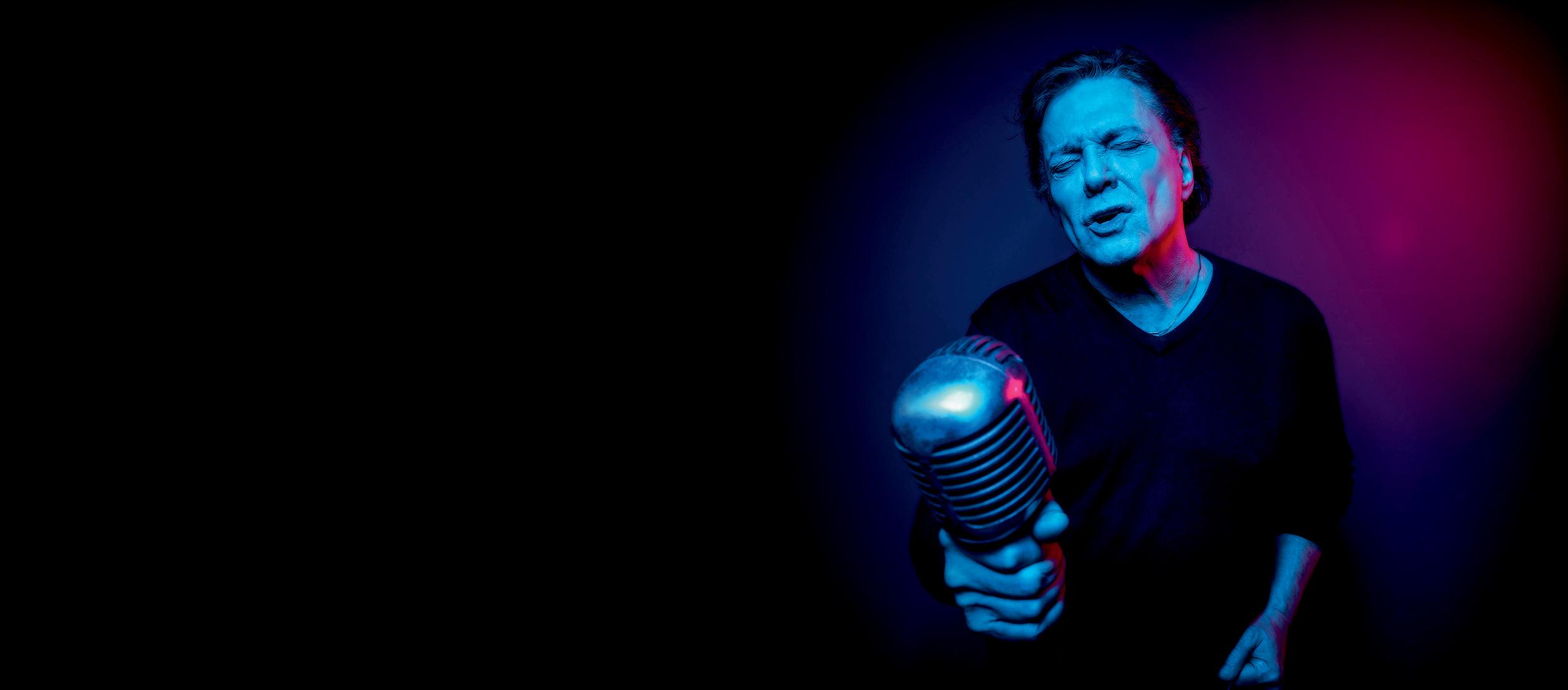 Fabio Jr num fundo escuro e bem azulado, segurando um microfone, de olhos fechados, cantando