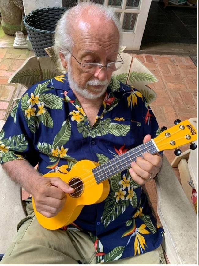 Homem idoso vestido uma camisa florida e tocando violão