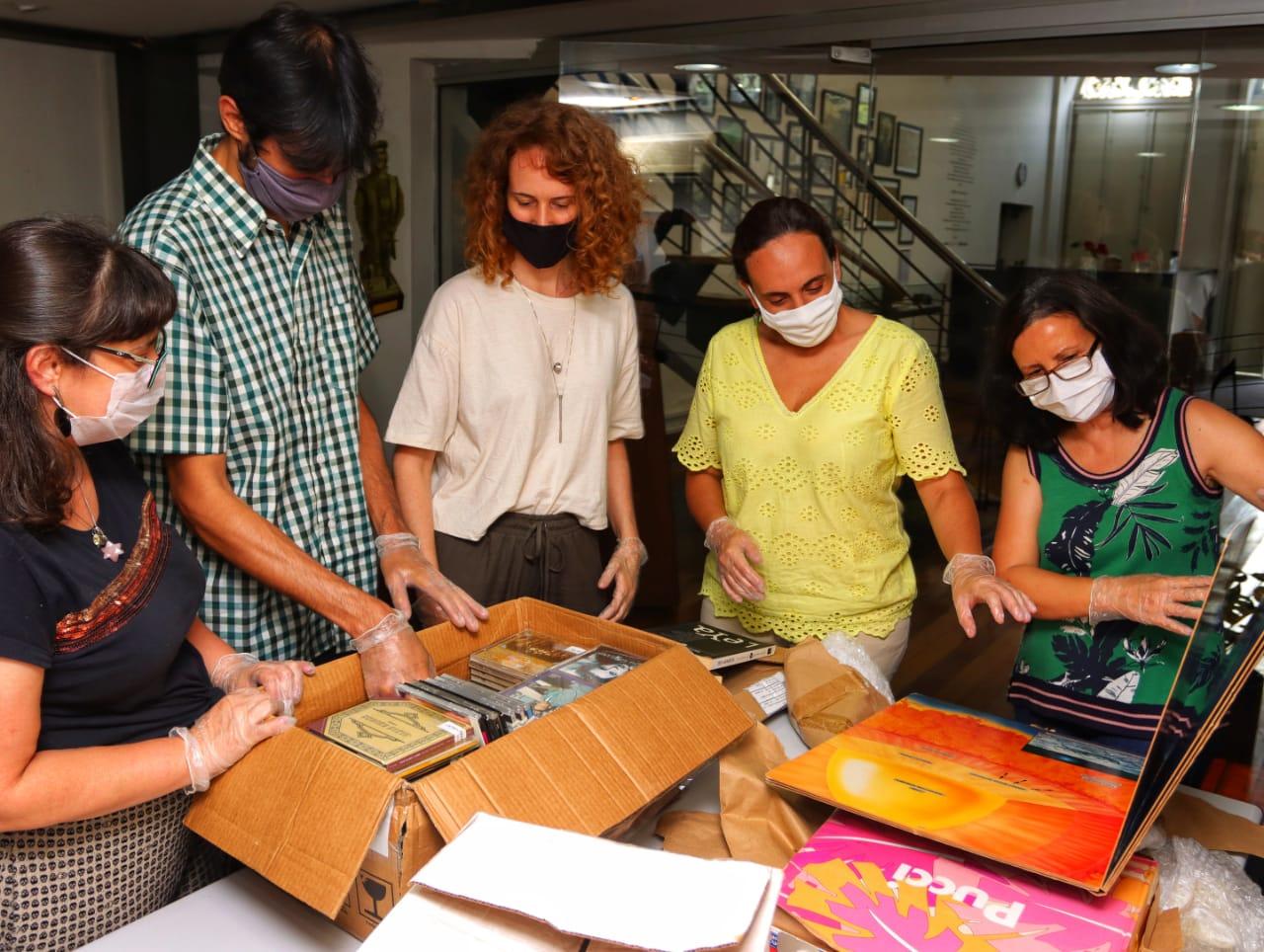 Cinco pessoas, de máscaras, analisam objetos como livros e discos dispostos em cima de uma mesa