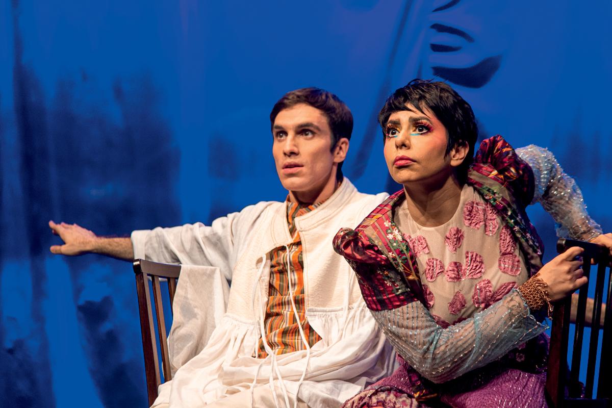 Um ator e uma atriz no palco, olhando para frente, com semblante atento. Eles vestem roupas coloridas