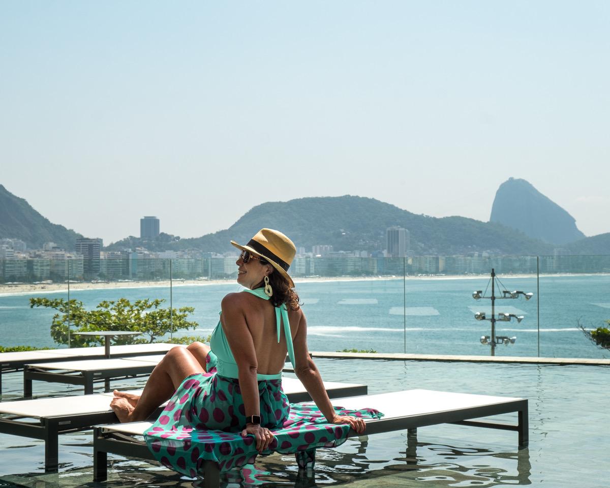 mulher de maiô e chapé panamá sentada em espreguiçadeira na beira da piscina. Vista para a Praia de Copacabana