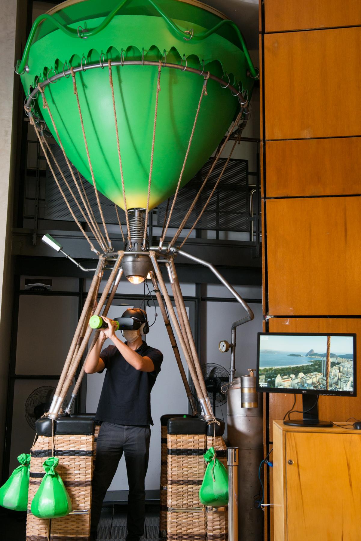 Homem munido de fones de ouvido e óculos de realidade virtual em balão cenográfico no Oi Futuro