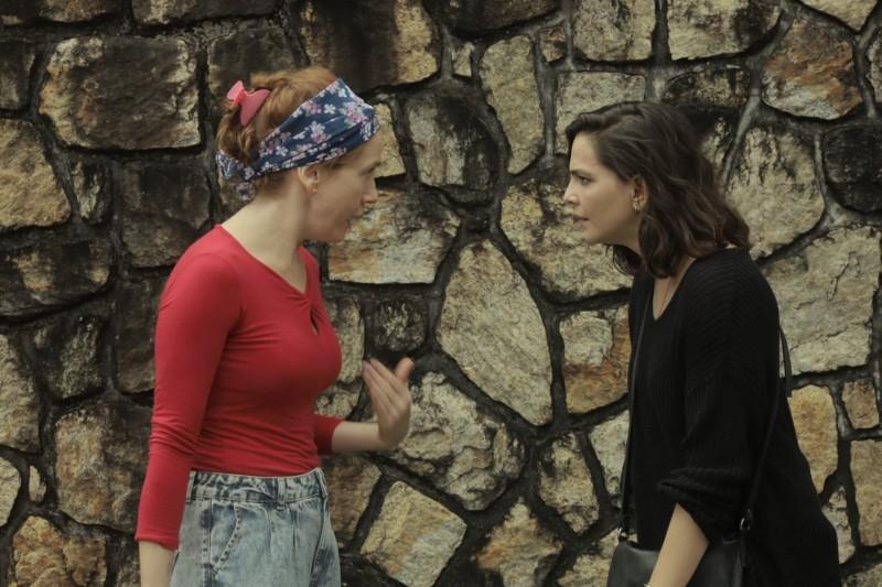 Personagens de Camila Morgado e Tainá Muller conversam em frente a um paredão de pedra