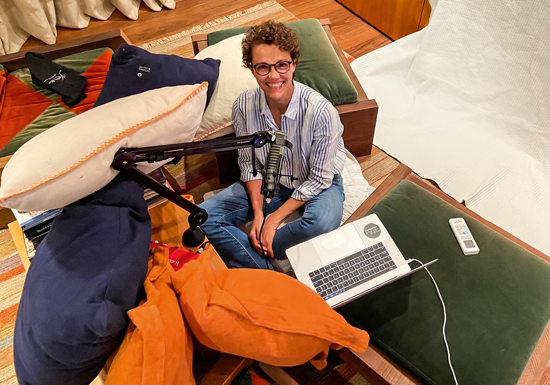 Branca Vianna em estúdio improvisado em casa, com microfone e computador em meio a várias almofadas