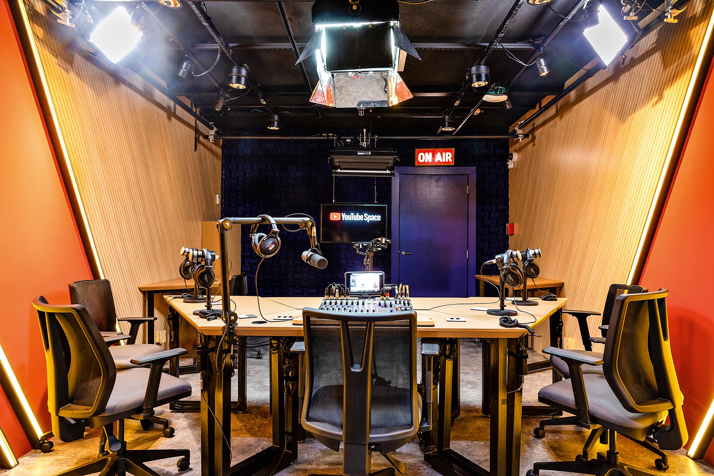 Estúdio de rádio no Youtube Space, com uma mesa ao centro, com vários microfones, cadeiras e refletores presos ao teto