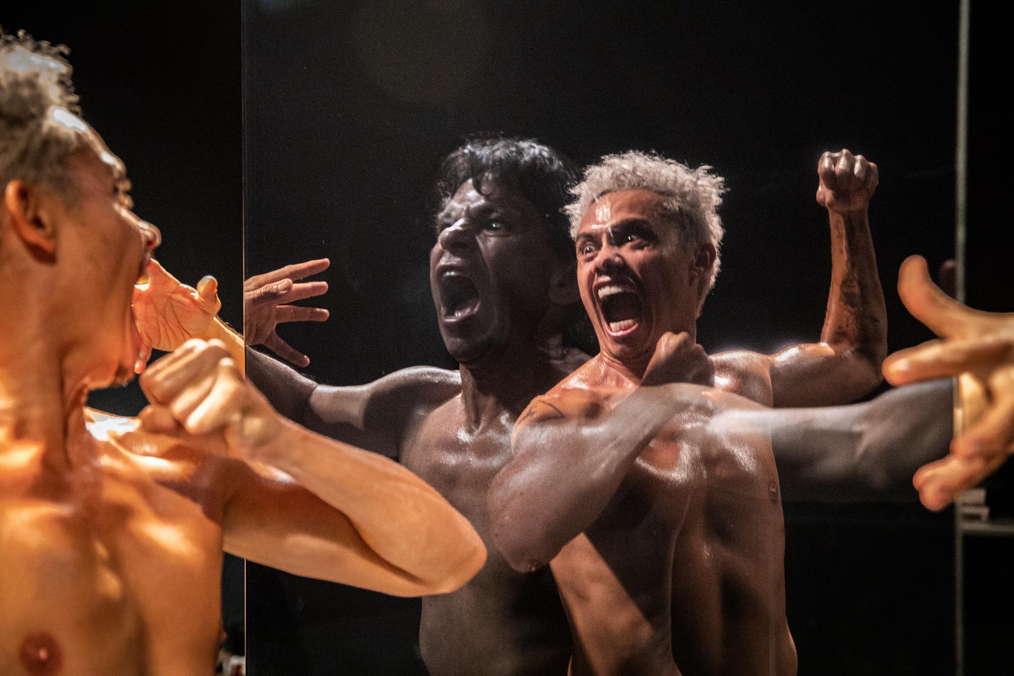 Dois atores, no palco, sem camisa fazem expressões como se estivessem gritando