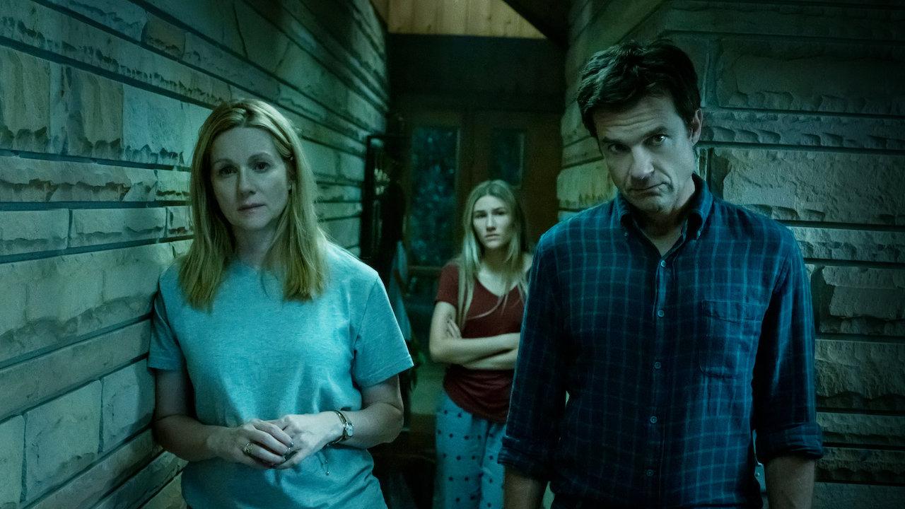 Personagens de Ozark olham para a câmera num ambiente inóspito, em tons escuros