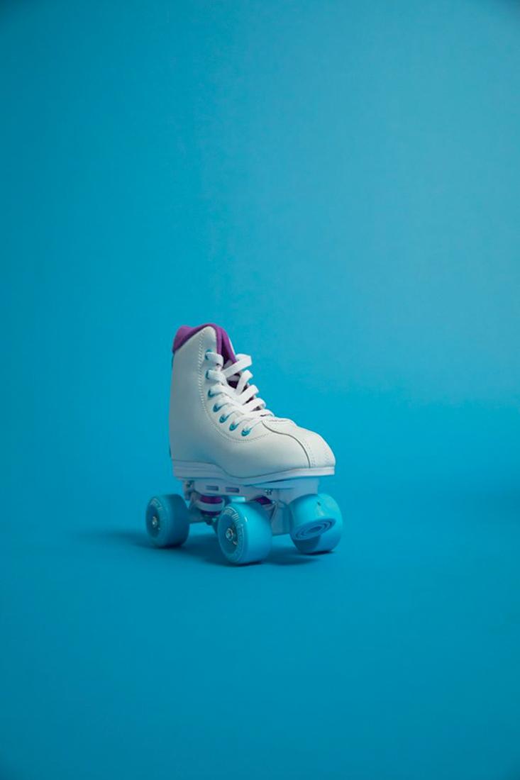 um pé de patins modelo retrô, branco de rodas azuis, num fundo azul