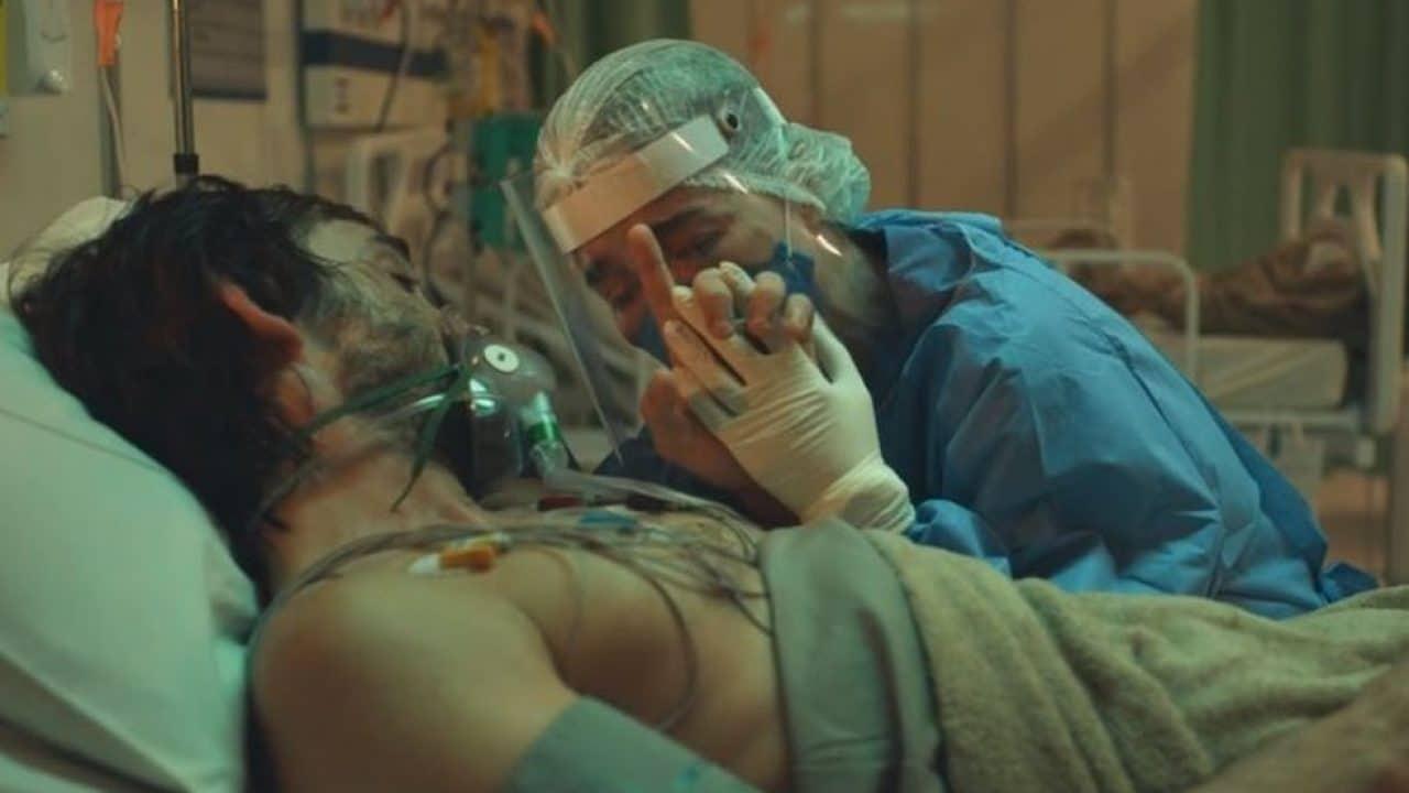 Personagens de Julio Andrade e Marjorie Estiano se abraçam. Ele está de máscara de oxigênio, num leito de UTI