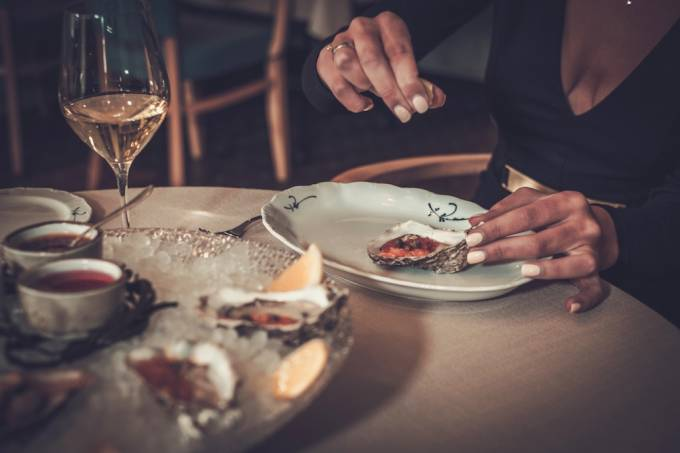 woman-eating-oysters-in-a-restaurant-PXRXU3V-1