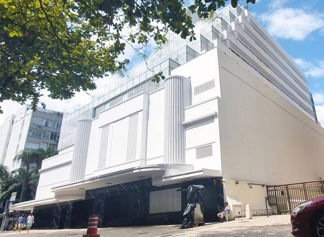 A imagem mostra a enorme fachada branca do Cine Leblon