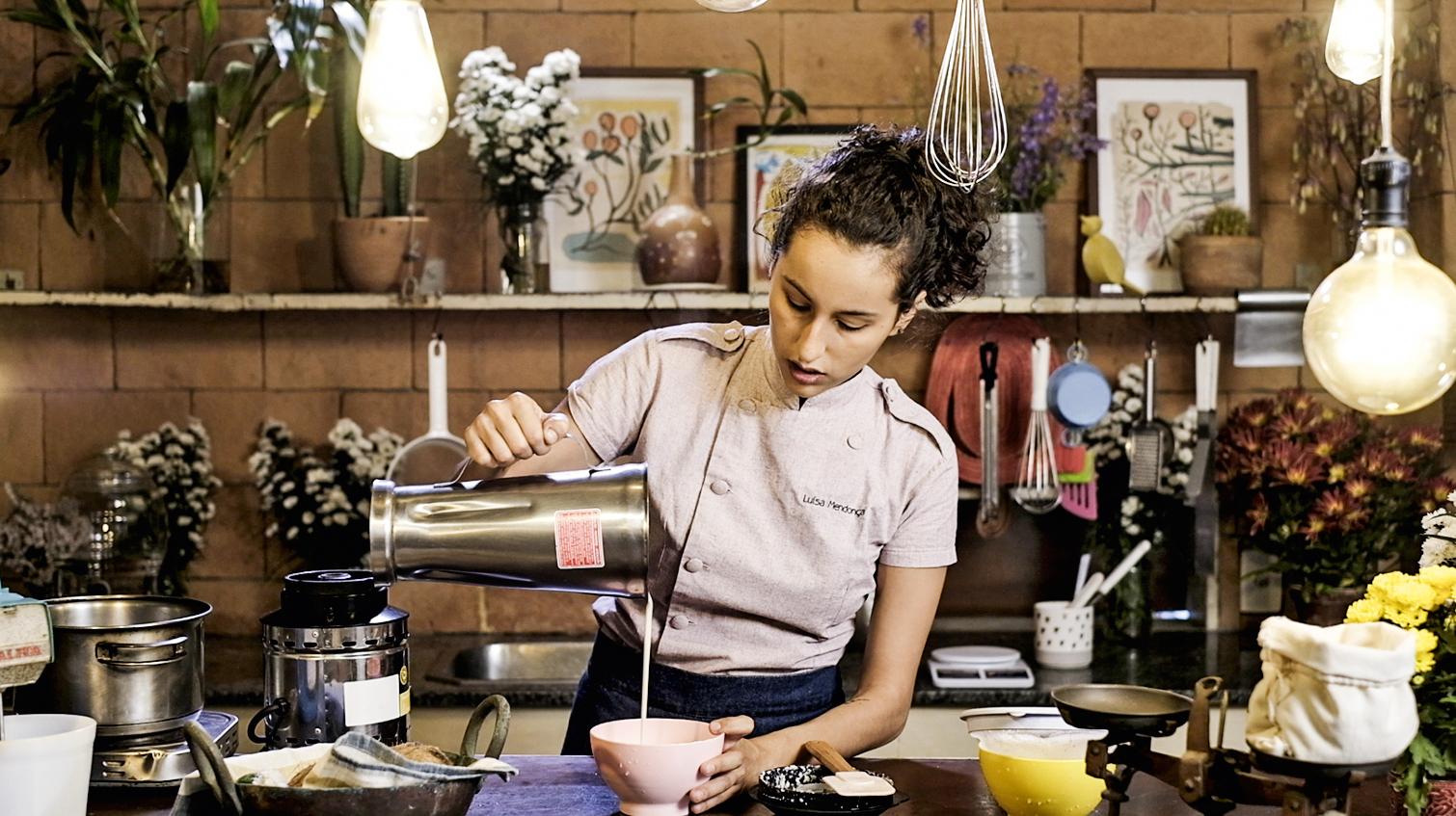 A imagem mostra a confeiteira vegana Luisa Mendonça na cozinha, despejando numa vasilha o leite vegetal que está no copo de um liquidificador