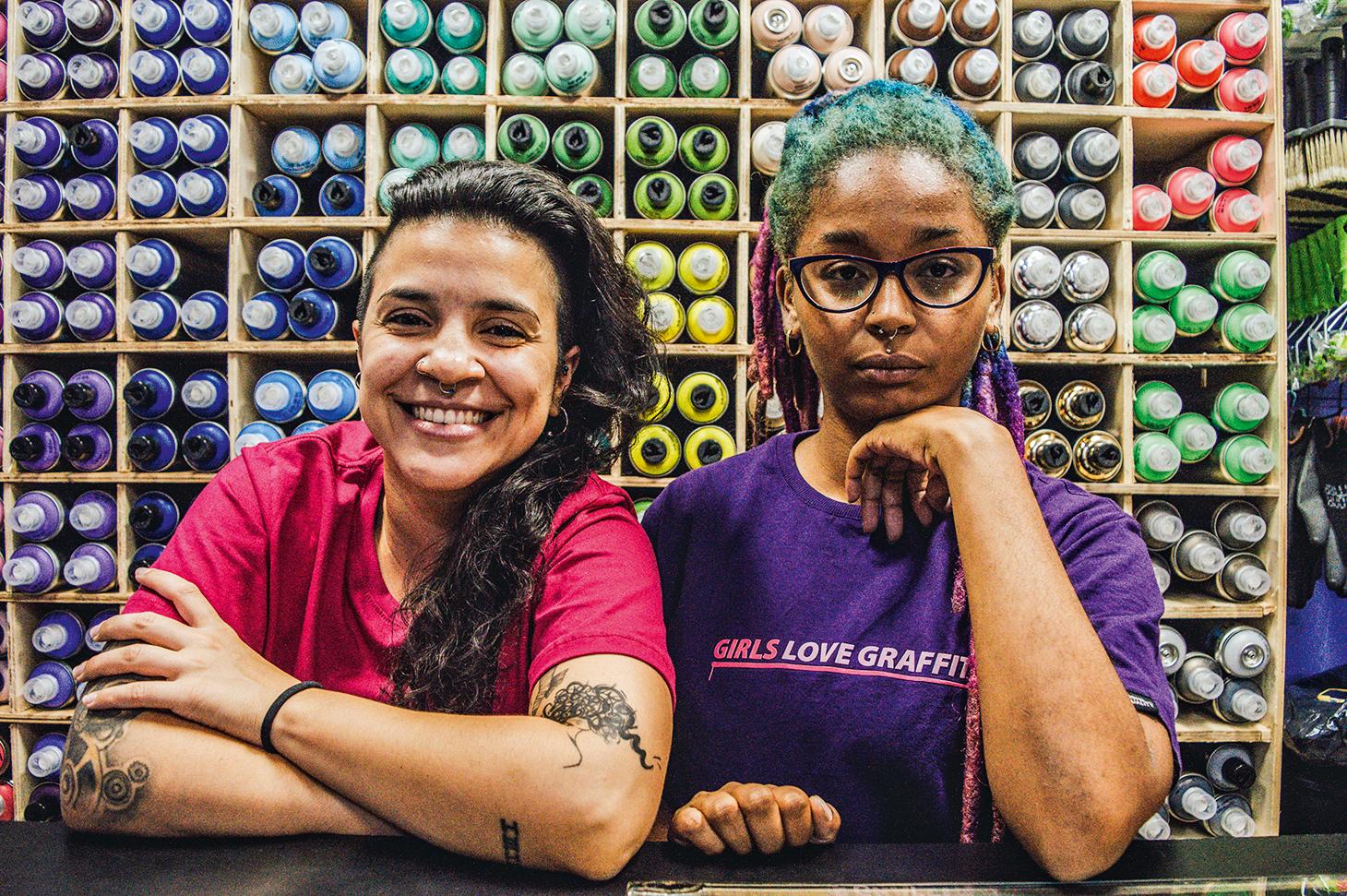 A imagem mostra Pâmela Matos e Leticia César apoiadas no balcão da loja de artigos para grafite que abriram juntas