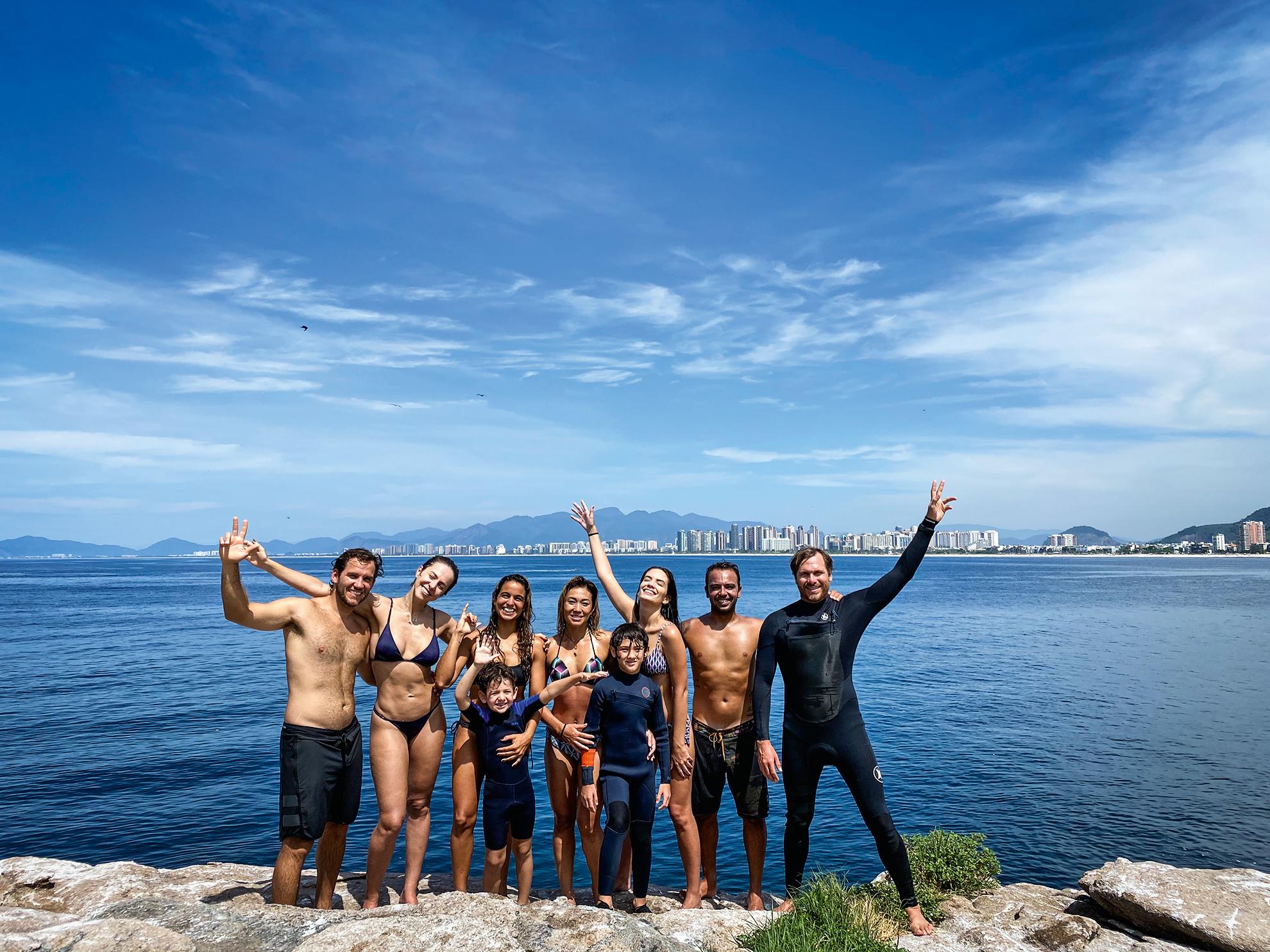 A imagem mostra um grupo de pessoas com traje de banho e roupa de mergulho acenando para a câmera à beira da Baía de Guanabara